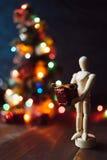 Träskyltdocka med gåvan och det Chritsmas trädet Royaltyfria Bilder