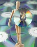 Träskyltdocka som bär en kompakt Disk Royaltyfri Fotografi