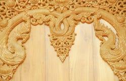 Träsnida med två nagamodeller på väggen i tempel arkivbild