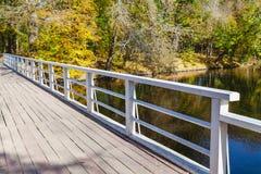 Träspång över floden om den ljusa höstdagen Fotografering för Bildbyråer