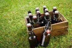 Träspjällåda med flaskor utan etikett av öl arkivbilder