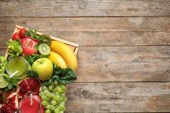Träspjällåda med fruktsafter i murarekrus och nya frukter på träbakgrund Utrymme f?r text arkivfoton