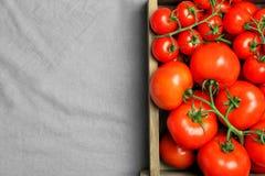 Träspjällåda med nya mogna tomater på grått tyg, bästa sikt Royaltyfri Bild