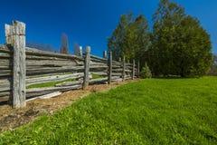 Trästaket i äng för grönt gräs Arkivfoto