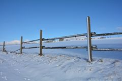 Trästaket i vinter med snö och blå himmel royaltyfri bild