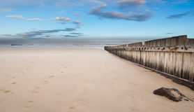 Trästaket på den tomma stranden på solnedgången Arkivfoton