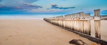 Trästaket på den tomma stranden på solnedgången Royaltyfria Bilder