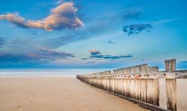 Trästaket på den tomma stranden på solnedgången Arkivfoto
