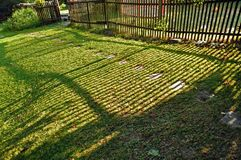 Trästaketet gör skuggor på en grön gräsmatta arkivfoton
