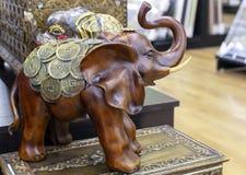 Trästatyett av en elefant som dekoreras med mynt arkivbilder