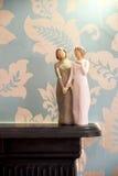 Trästatyn av två kvinnor som rymmer händer, staty är på en svart Arkivfoto