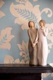 Trästatyn av två kvinnor som rymmer händer, staty är på en svart Arkivfoton