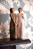 Trästatyn av två kvinnor som rymmer händer, staty är på en svart Royaltyfria Foton