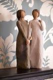 Trästatyn av två kvinnor som rymmer händer, staty är på en svart Royaltyfria Bilder