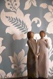 Trästatyn av två kvinnor som rymmer händer, staty är på en svart Arkivbild