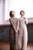 Trästatyn av två kvinnor som rymmer händer, staty är på en svart M Arkivfoto