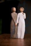 Trästatyn av två kvinnor som rymmer händer, staty är på en svart M Arkivfoton