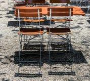Trästolar och tabeller parkerar in kafét Arkivbild