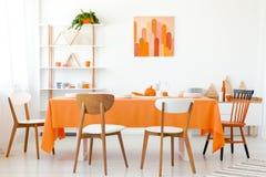 Trästolar på den orange tabellen i vit matsal arkivbild