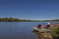 Trästolar på en sjö Royaltyfri Bild