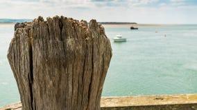 Trästolpe med skepp i bakgrunden, Wales, UK Arkivfoto