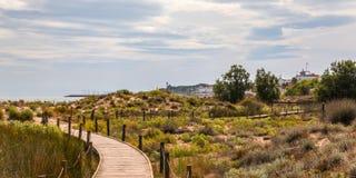 Trästrandpromenad i dyerna som leder till den sandiga stranden, PA Arkivbilder