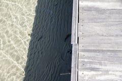 Trästrandpromenad på genomskinligt havsvatten med sand på botten fotografering för bildbyråer