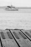 Trästrandpromenaden som ser till ett skepp, förtöjde i hamnen Royaltyfri Foto