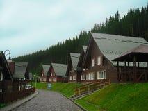 Trästugor i berg och skog under blå himmel royaltyfri fotografi
