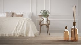 Trätabellöverkant eller hylla med aromatiska pinneflaskor över klassiskt sovrum för suddig tappning med blan mjuk säng som är ful fotografering för bildbyråer