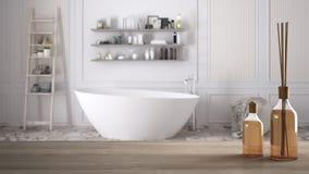 Trätabellöverkant eller hylla med aromatiska pinneflaskor över suddigt klassiskt badrum med badkaret, vit arkitekturinre arkivbild