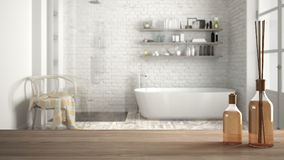 Trätabellöverkant eller hylla med aromatiska pinneflaskor över suddigt klassiskt badrum med badkaret, vit arkitekturinre royaltyfri foto