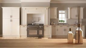 Trätabellöverkant eller hylla med aromatiska pinneflaskor över suddigt klassiskt kök med ön, vit arkitekturinre arkivbilder