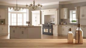 Trätabellöverkant eller hylla med aromatiska pinneflaskor över suddigt klassiskt kök med ön, vit arkitekturinredesig Royaltyfri Fotografi