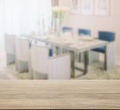Trätabellöverkant med suddighet av att äta middag tabellen och bekväm stol royaltyfria bilder