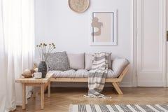 Trätabell bredvid beige soffa med filten i ljus vardagsruminre med affischen Verkligt foto royaltyfria bilder