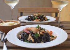 Trätabell för havs- för Alioli för vitt vin för räka för closeup för tioarmad bläckfiskfärgpulverpasta terrass restaurang royaltyfria bilder