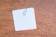 trätabell för paperclip för anmärkningspapper Arkivbilder