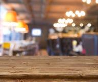 Trätabell framme av abstrakt suddig resturant ljusbakgrund Royaltyfri Fotografi