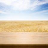 Trätabell med bakgrund för vetefält Blå himmel över moget gult vetefält Sommarbakgrund, förlöjligar upp för design Arkivfoto