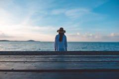 Trätabell med bakgrunden för hav och för blå himmel och en suddighetskvinna fotografering för bildbyråer