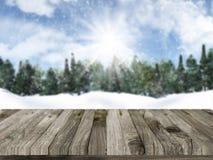 Trätabell med defocussed snöig landskap för jul i lodisarna Arkivfoto
