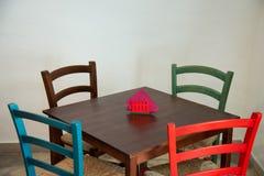 Trätabell med färgrika stolar i en restaurang fotografering för bildbyråer