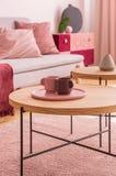Trätabell med koppar på plattan på rosa matta i vardagsrum som är inre med den gråa soffan Verkligt foto arkivfoton