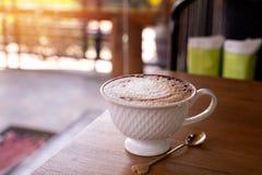 Trätabell med koppen av lattekaffe i morgon arkivbild