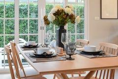 Trätabell och stolar i matsal med den eleganta tabellinställningen Arkivfoton