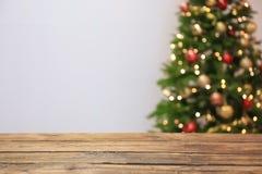 Trätabell och suddig julgran royaltyfri fotografi