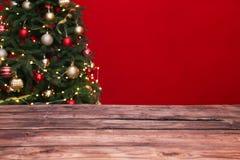 Trätabell och suddig julgran med felika ljus royaltyfri bild