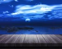 Trätabell som ut ser till havet på natten Royaltyfria Bilder