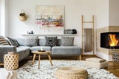 Trätabellen bredvid grå färger tränga någon soffan i varm vardagsruminte royaltyfri bild